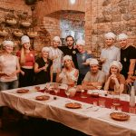 A group of people posing for a photo in a restuarant wearing chefs hats